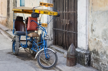 crumbling: Street scene in Havana with an  old bicycle and shabby buildings