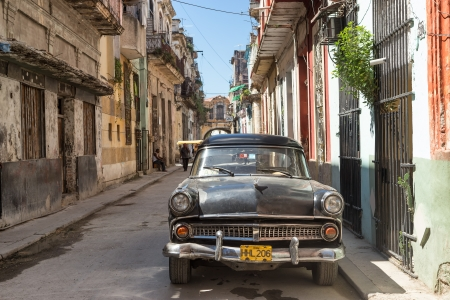 Old american car in a street sidelined with decaying buildings in Havana These cars,still in use after many decades,have become a worldwide known symbol of Havana Stock Photo - 22948657