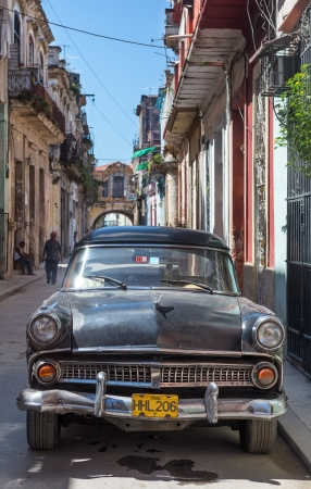 Old american car in a street sidelined with decaying buildings  in Havana These cars,still in use after many decades,have become a worldwide known symbol of Havana Stock Photo - 22948658
