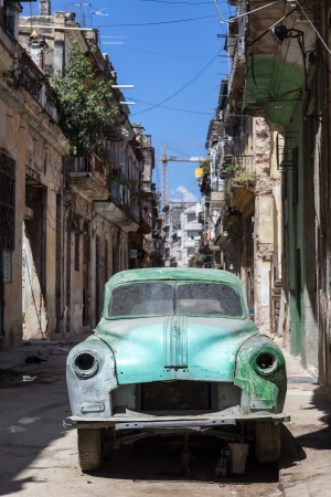 Rusty and broken old american car abandoned in a shabby street  in Havana These cars,thousands of them still in use after many decades,have become a symbol of Havana Stock Photo - 22991318