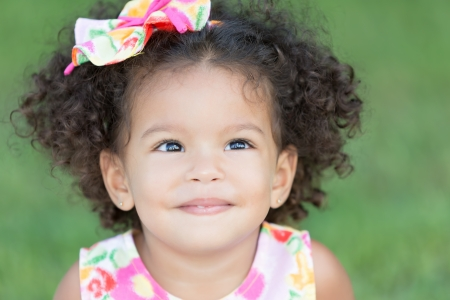 diffused: Portrait of a cute latin girl wearing a colorful dress and smiling with a diffused green grass background