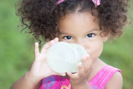 baby hairstyle: Funny and cute latin girl drinking from a baby bottle with a diffused green grass background