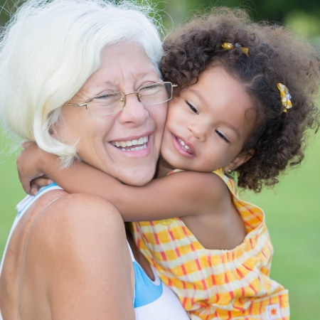 Grandmother hugs her hispanic granddaughter on a park Stock Photo