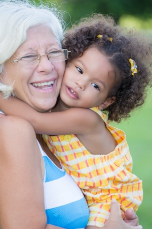 Grandmother hugs her hispanic granddaughter and laughs  with a diffused green grass background  photo