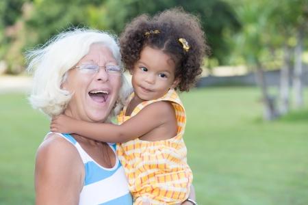 abuela: Retrato de una abuela cauc�sico que lleva a su peque�a nieta hispana y riendo