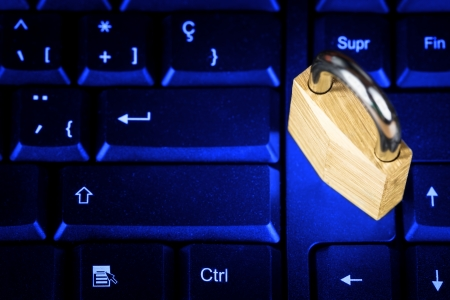 cryptography: Locked padlock on a black computer keyboard with a glowing blue lightning