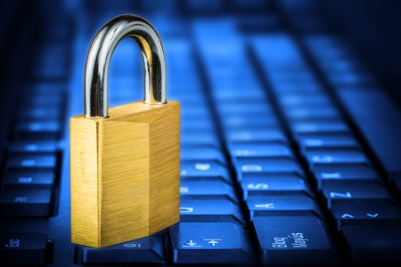 sabotage: Locked padlock om a glowing blue computer keyboard useful to illustrate data security