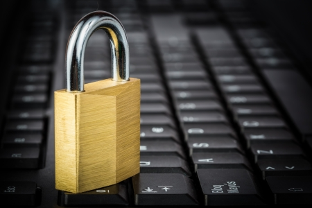 cryptography: Closed golden padlock on a black computer keyboard Stock Photo