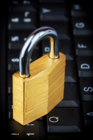 Closed golden padlock on a black computer keyboard photo