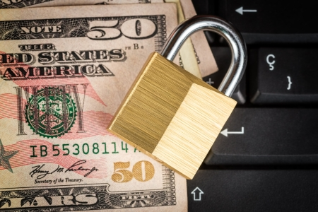 Closed padlock over a stack of money on a black computer keyboard - useful to illustrate financial data security photo