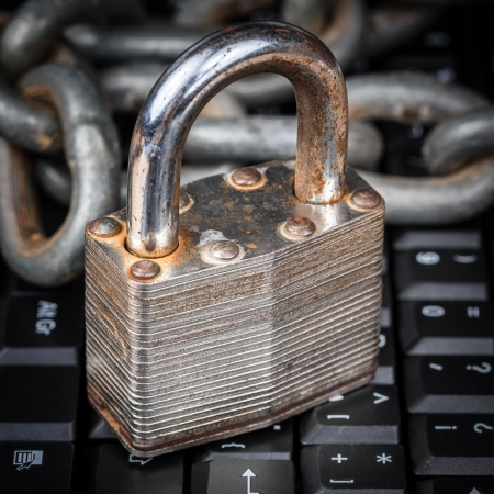 Old rusty padlock and chain on a computer keyboard - data security Stock Photo - 23692032