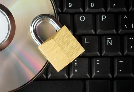 Candado cerrado y DVD en un teclado de computadora útiles para ilustrar la seguridad de datos