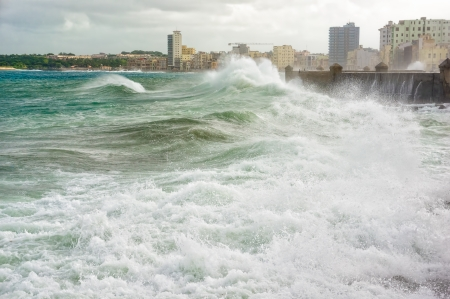 windy city: Hurricane in Havana with huge waves hitting the sea wall and a view of the skyline
