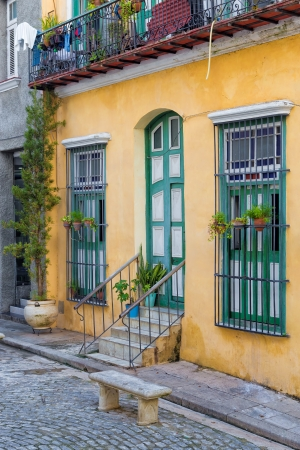 cobbled: Colorful traditional house in Old Havana with flower pots and plants on its windows
