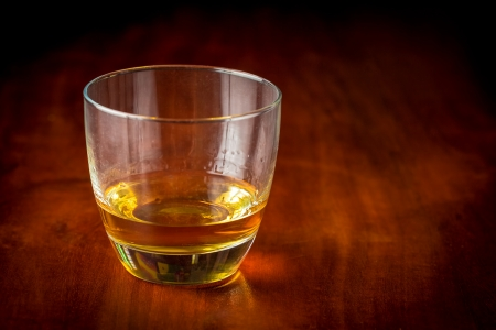 Glass of whisky or rum on a wooden table  with beautiful golden lighting  photo