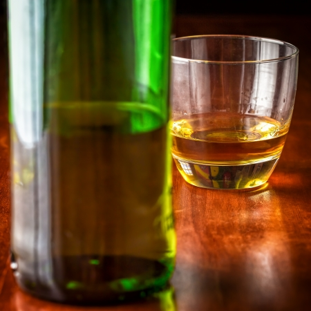 Glass of whisky or rum and a green liquor bottle on a wooden table  with beautiful golden lighting  photo