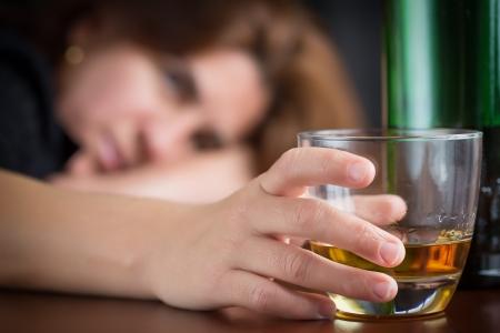 酔って女性の彼女の顔のウィスキーまたはラム酒のガラスを保持フォーカスが合っていません。