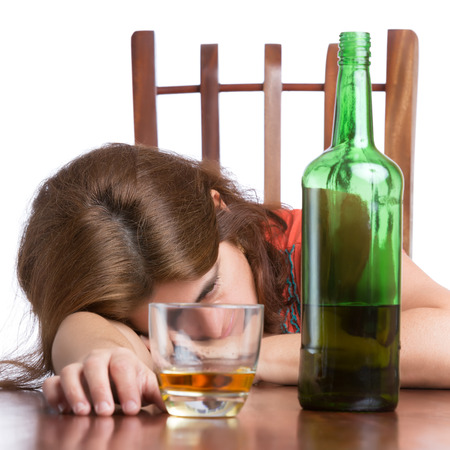 alcoholism: Drunk,sad and tired woman with a bottle of scotch isolated on white Stock Photo