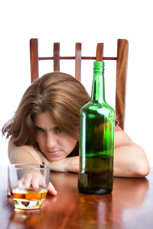 Drunk,sad and depressed woman with a bottle of scotch isolated on white