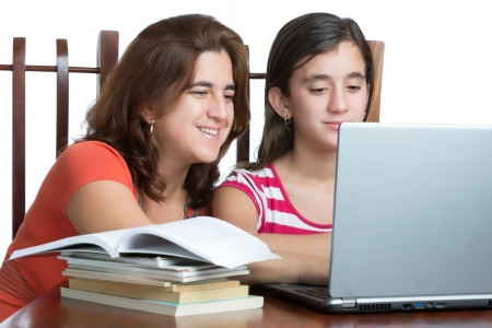 child studying: Hispanic teen and her mother working or browsing the web on a laptop computer isolated on white