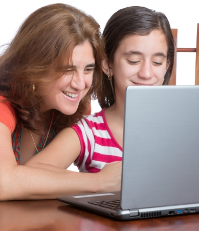 Teenager and her mother working on a laptop computer or browsing the web isolated on white photo