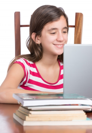 Teenager doing homework or browsing the web on her laptop isolated on a white background photo