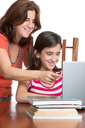 Hispanic teen and her mother browsing the web and laughing on a laptop computer isolated on white photo