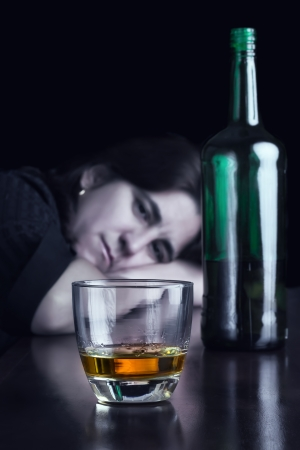 Blue toned dark image of a sad drunk woman staring at a glass of whisky photo