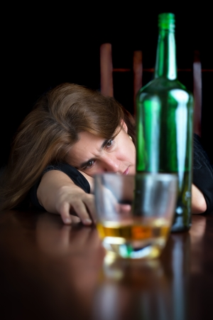 Dark emotional image of a sad drunk woman with a glass of whisky photo
