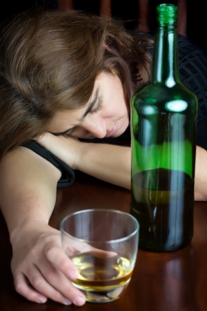 Dramatic image of a drunk woman sleeping and holding a glass of whisky photo