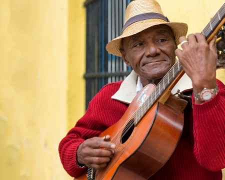 Old afrocuban street musician playing the guitar next to a colonial house in Cuba