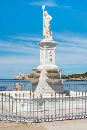 Statue of Neptune in the bay of Havana with the castle of El Morro  photo