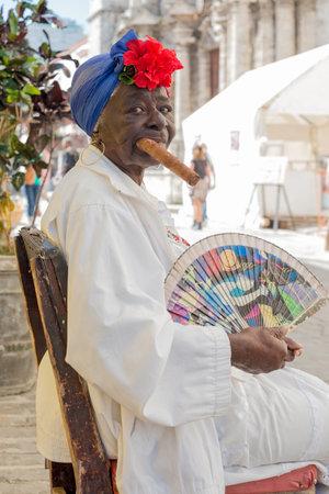 cigarro: Anciana negro fumando un enorme puro cubano junto a la catedral de la habana Personajes como este son una vista común en las calles de La Habana Vieja