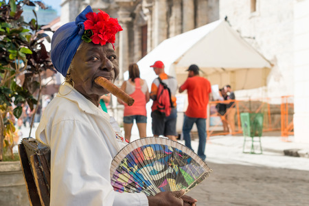 Old black lady smoking a huge cuban cigar next to the havana Cathedral Characters like this are a common sight in the streets of Old Havana Editorial