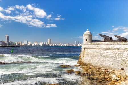 Tower and cannons of the castle of El Morro with the Havana skyline  photo