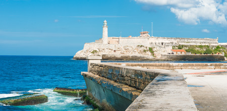 The castle of El Morro in Havana and the famous  wall of Malecon with white puffy clouds on a blue sky photo