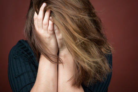 Adult woman crying with her hands covering her face photo