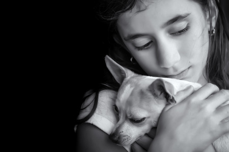 sad lonely girl: Emotional black and white portrait of a sad lonely girl hugging her small dog