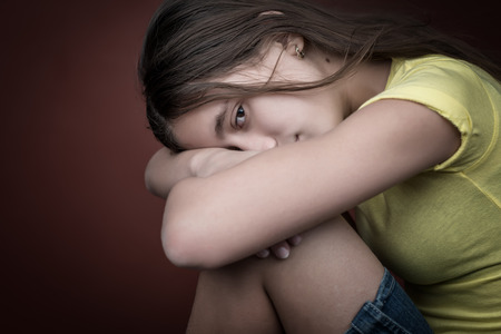 youth background: Sad and lonely girl with her head resting on her legs and looking at the camera