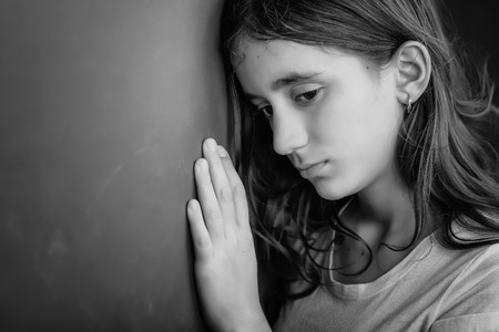 alone and sad: Grunge black and white portrait of a sad girl leaning against a wall Stock Photo