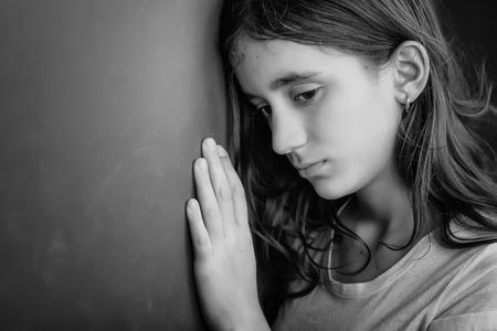 maltrato infantil: Grunge retrato en blanco y negro de una ni�a triste apoy�ndose contra una pared