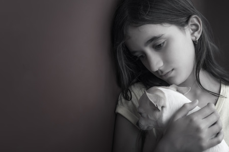 preteen girl: Sad and lonely girl and her small dog leaning against a wall Stock Photo