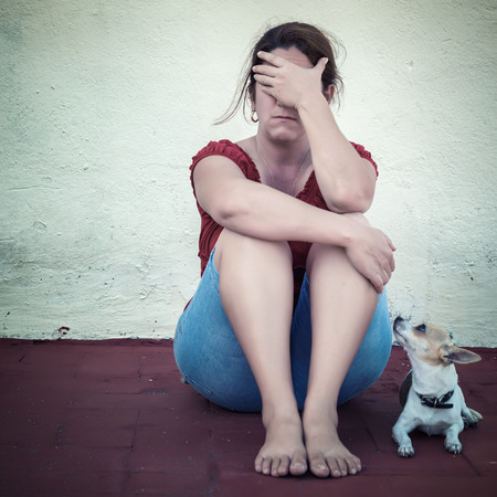 Sad adult woman crying with a small dog besides her