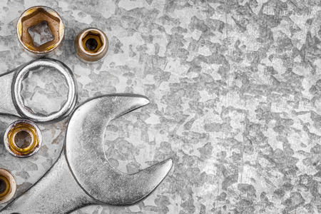 Wrench tools and nuts on a light textured metallic background with space for text Stock Photo
