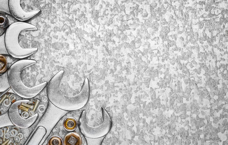 automotive industry: Wrench tools and nuts on a light textured metallic background with space for text Stock Photo