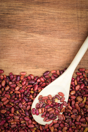 leguminosae: Red beans and a wooden spoon on a wood background with space for text