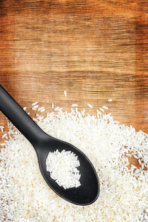 Spoon and white rice grains on a vintage wooden background photo