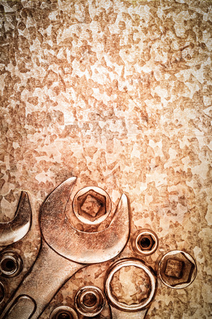 Wrench tools and nuts on a vintage metallic background with space for text photo