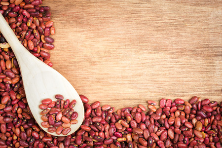 leguminosae: Raw red beans and a spoon framing a wooden background with space for text Stock Photo