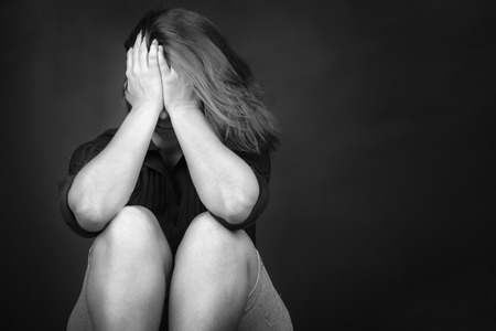 Black and white image of a very sad young woman useful to illustrate stress, depression or domestic violence